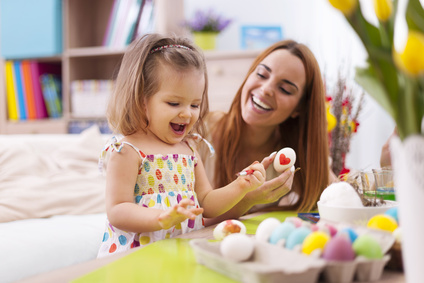 Loving mother and her baby painting easter eggs